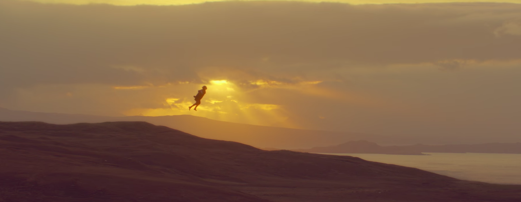 harry styles flying infront of sunset